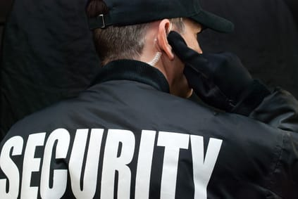 Security Guard Listens To Earpiece, Back of Jacket Showing